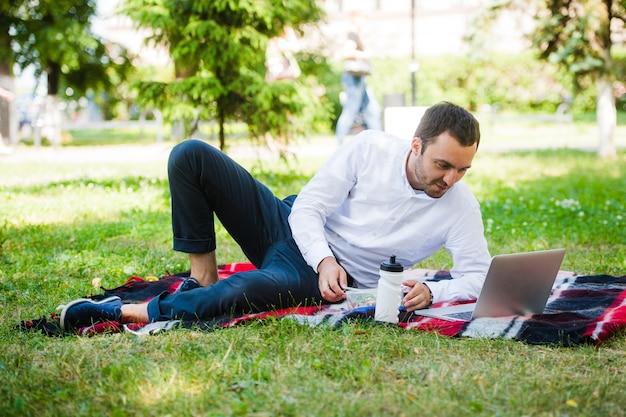 Uomo d'affari che lavora in giardino e pranza
