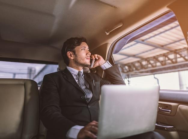 Uomo d'affari che lavora al suo computer portatile e parlando al telefono