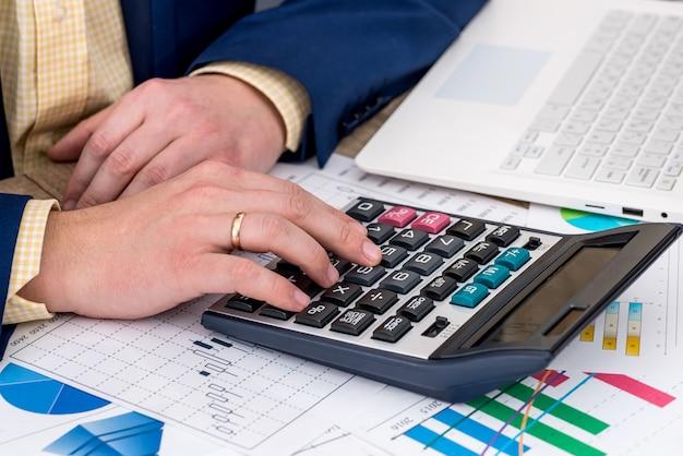 Uomo d'affari che lavora al computer portatile con il grafico commerciale