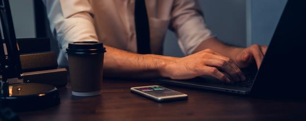 Uomo d'affari che lavora al computer portatile e analisi grafici linea di candela schermo sullo smartphone in ufficio nella notte.