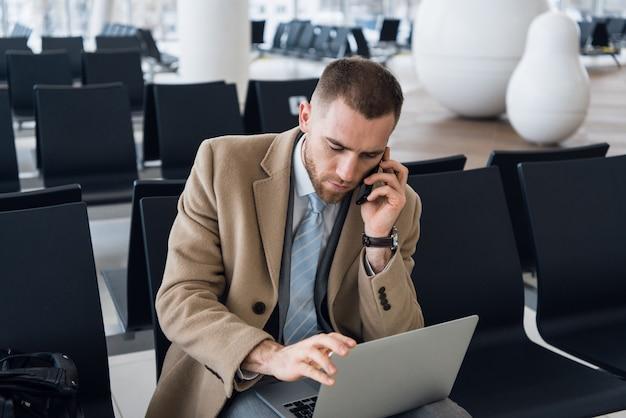 Uomo d'affari che lavora al computer portatile e che parla sul cellulare al salotto aspettante dell'aeroporto.
