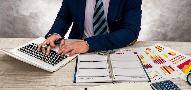 Uomo d'affari che lavora in ufficio con grafici aziendali, laptop e blocco note.