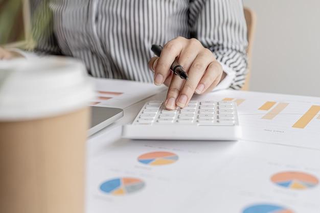 Imprenditrice che lavora in un ufficio privato, sta esaminando i documenti finanziari dell'azienda inviati dal dipartimento finanziario prima che lui li porti a un incontro con un partner commerciale. concetto finanziario.
