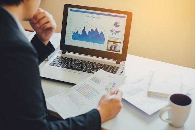 Uomo d'affari che lavora sul risultato del progetto per analizzare i dati del rapporto finanziario dell'azienda