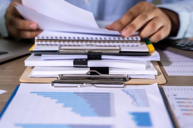 I documenti della lettura di lavoro dell'uomo d'affari rappresentano grafici finanziari ai successi di lavoro analizzano i piani del documento