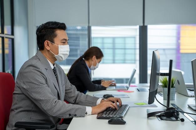 Uomo d'affari che lavora e indossa una maschera per proteggere la malattia da virus corona covid-19 o dall'ufficio modello.