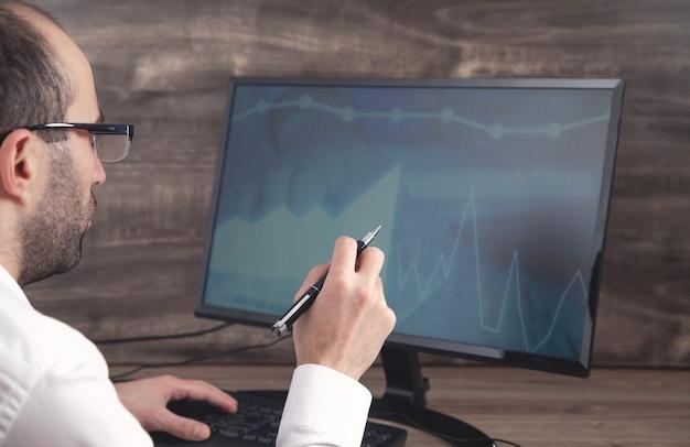 Uomo d'affari che lavora con analisi seduto al posto di lavoro con il computer. grafici e grafici sullo schermo del computer. attività commerciale. finanza. contabilità
