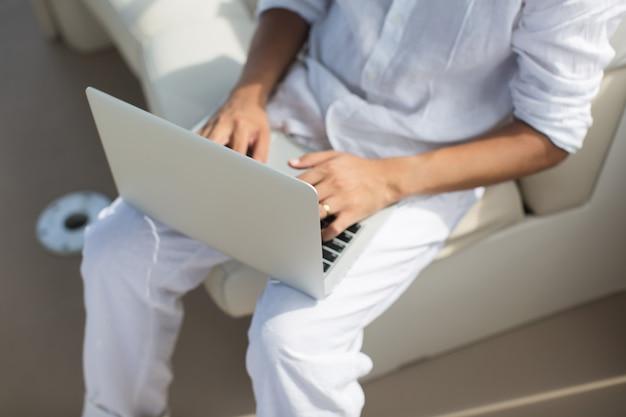 Uomo d'affari che lavora con il computer su una barca, un bel ufficio all'aperto