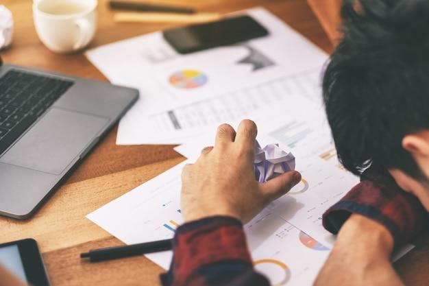 Un uomo d'affari che lavora sentendosi frustrato e stressato con documenti e laptop rovinati sul tavolo in ufficio