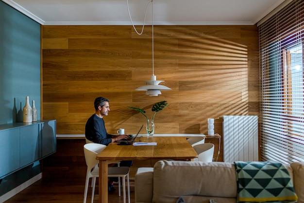 Uomo d'affari che lavora con il computer portatile nel suo soggiorno