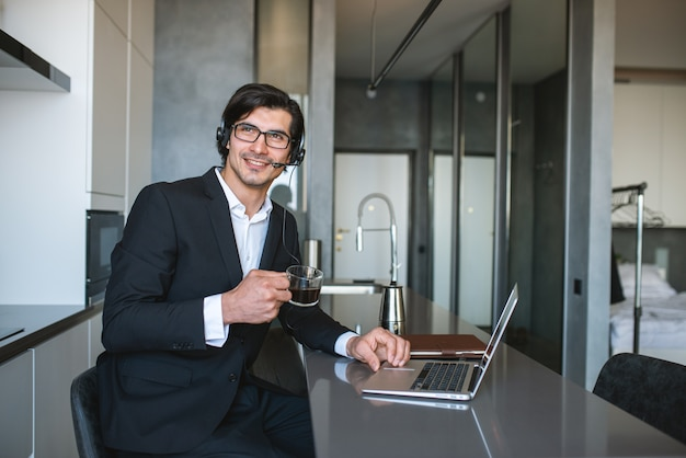 L'uomo d'affari lavora da casa con un computer portatile