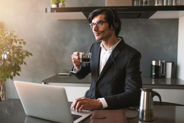 L'uomo d'affari lavora da remoto a casa con un laptop a causa della quarantena del coronavirus.