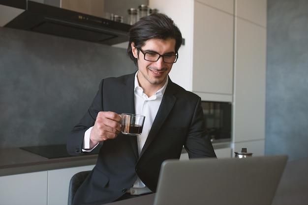 L'uomo d'affari lavora a distanza a casa con un computer portatile