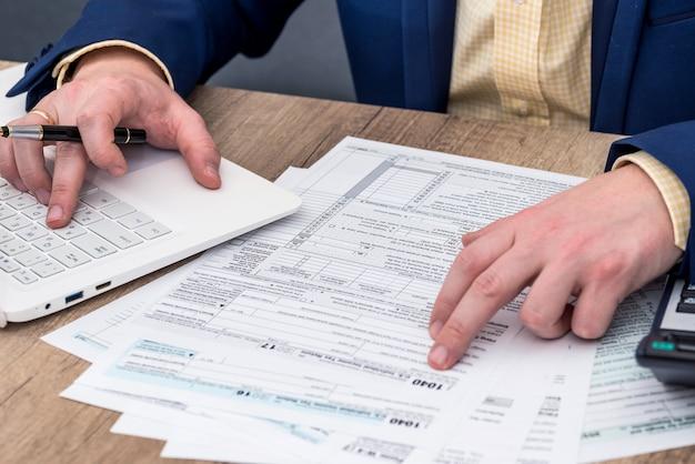 L'uomo d'affari lavora con 1040 modulo fiscale, laptop e calcolatrice