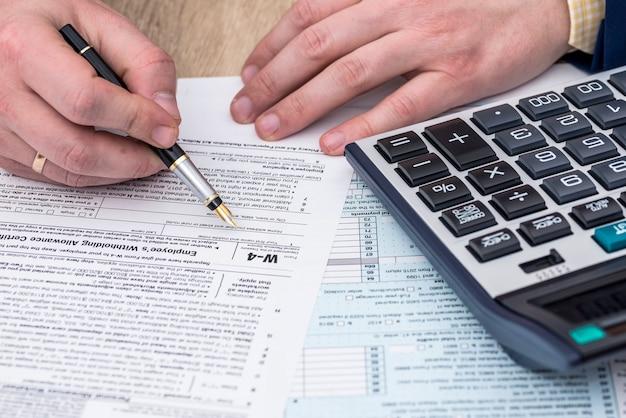 L'uomo d'affari lavora con il modulo fiscale w-4 e la calcolatrice
