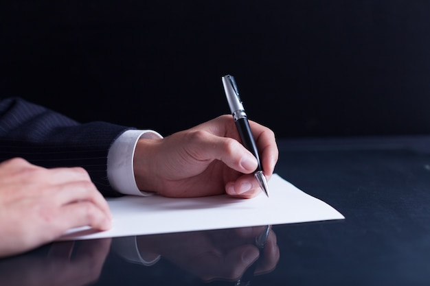 Uomo d'affari che scrive una lettera, note o corrispondenza o firma un documento o un accordo,