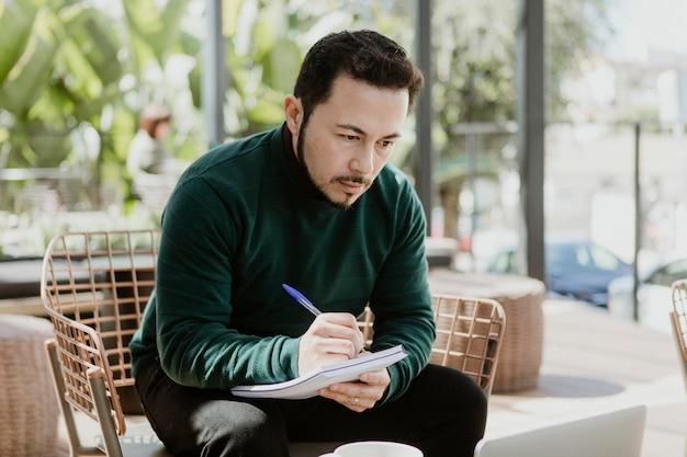 Uomo d'affari che scrive su un taccuino in un caffè