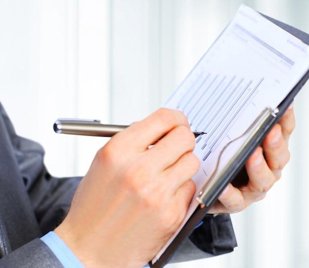 Uomo d'affari che scrive qualcosa sulla carta