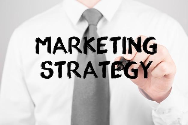 Imprenditore la scrittura di parola strategia di marketing con un pennarello, la concezione di business