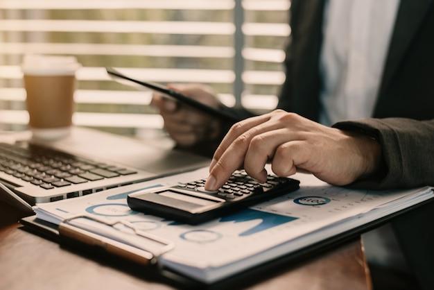 Gli uomini d'affari stanno calcolando le spese di reddito e analizzando i dati sugli investimenti immobiliari in ufficio.