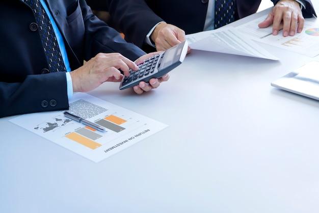 Gli uomini d'affari stanno esaminando a fondo un rapporto finanziario per un ritorno sull'investimento o un'analisi del rischio di investimento su una scrivania bianca. spazio di copia in basso a destra incluso.