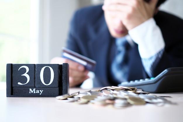 Gli uomini d'affari sono stressati con la fine del mese a pagare per le carte di credito