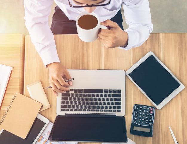 Gli uomini d'affari stanno lavorando su computer portatili e bevendo caffè, vista dall'alto.