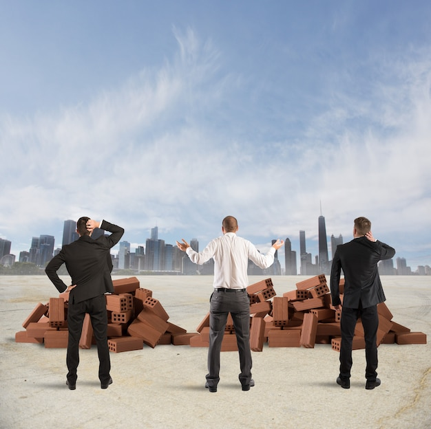 Gli uomini d'affari guardano confusi un edificio in mattoni in frantumi