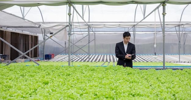 Gli uomini d'affari esaminano e registrano i rapporti sulla qualità degli ortaggi biologici dell'azienda.