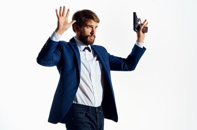 Pistola degli uomini d'affari nelle mani dello sfondo chiaro dell'agente delle emozioni della mafia