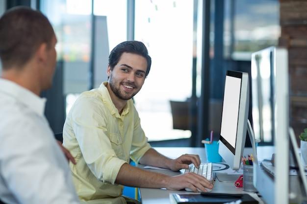Uomini d'affari che interagiscono mentre si lavora su personal computer
