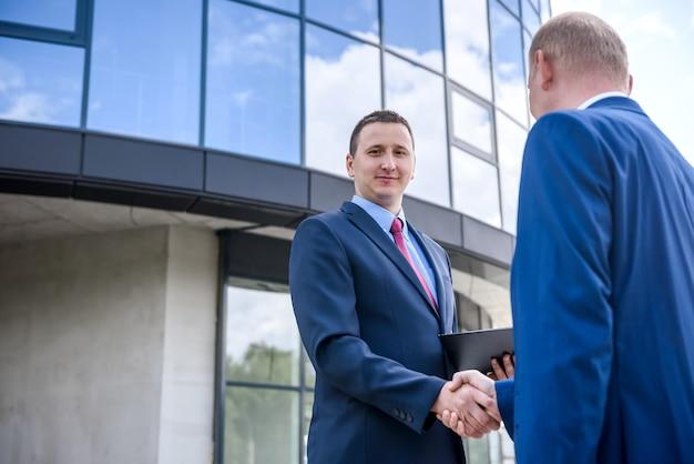 Uomini d'affari che fanno affari e si stringono la mano all'esterno dell'edificio Foto Premium