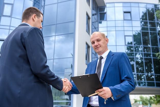 Uomini d'affari che fanno affari e si stringono la mano fuori dall'edificio