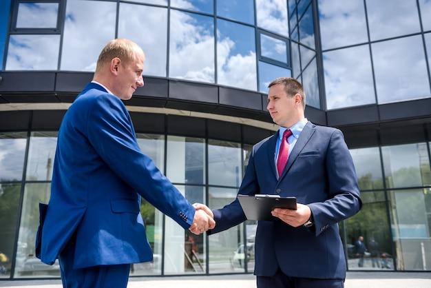 Uomini d'affari che fanno affare e handshake all'esterno dell'edificio