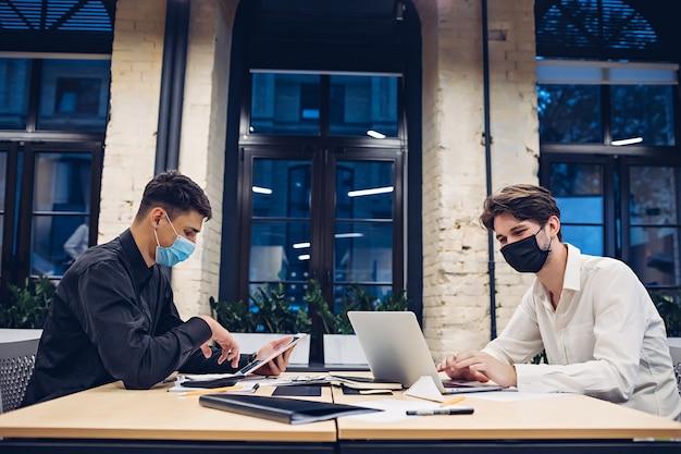 Uomini d'affari in maschere mediche che lavorano in ufficio