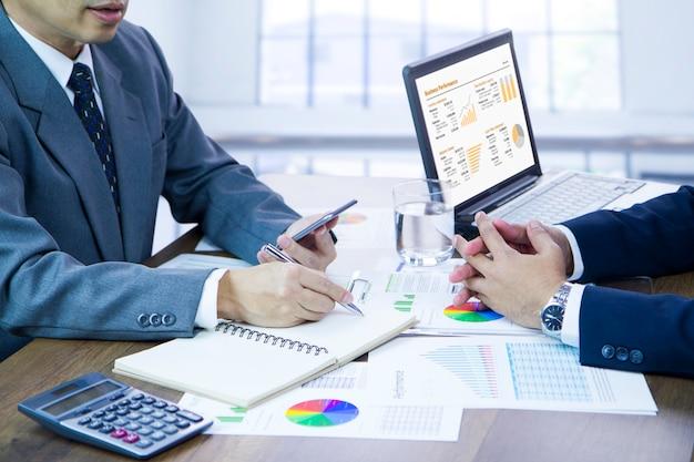 Uomini d'affari che esaminano le prestazioni aziendali e pianificano gli obiettivi per un nuovo anno di bilancio.