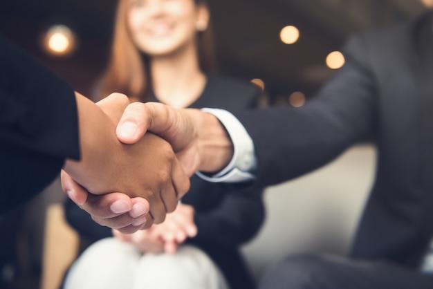 Uomini d'affari che agitano le mani dopo l'incontro in un caffè
