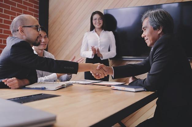 Uomini d'affari che agitano le mani insieme felici. dopo i negoziati hanno avuto successo