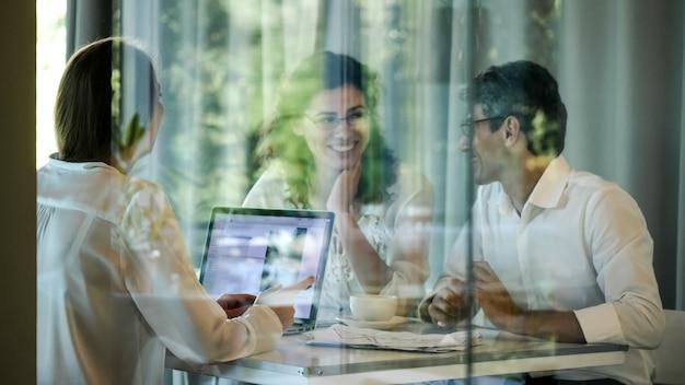 Gli uomini d'affari si siedono a un tavolo in una stanza dietro una parete di vetro. gli imprenditori stanno discutendo un nuovo progetto nella sala riunioni.
