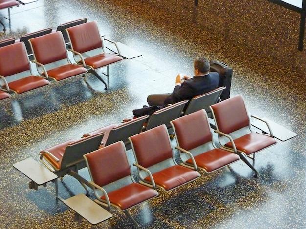 Uomini d'affari che aspettano da soli il suo volo lavorando con il suo pocket pc