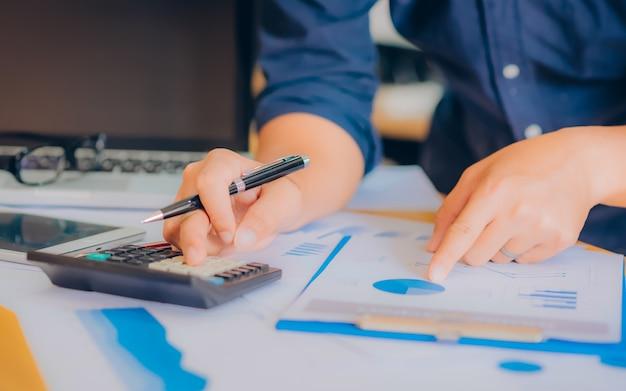 Gli uomini d'affari utilizzano la calcolatrice per calcolare e analizzare il comp