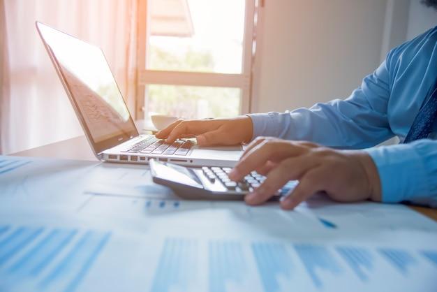 Gli uomini d'affari usano la calcolatrice per calcolare e analizzare il comp