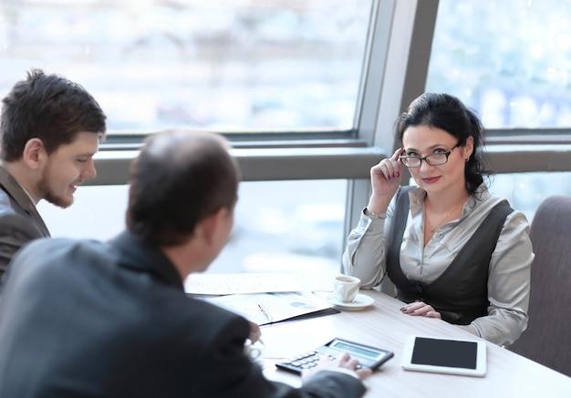 Gli uomini d'affari usano la calcolatrice per discutere i grafici delle analisi
