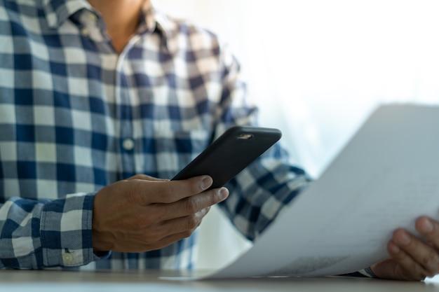 Gli uomini d'affari usano i telefoni per pagare le bollette attraverso le applicazioni