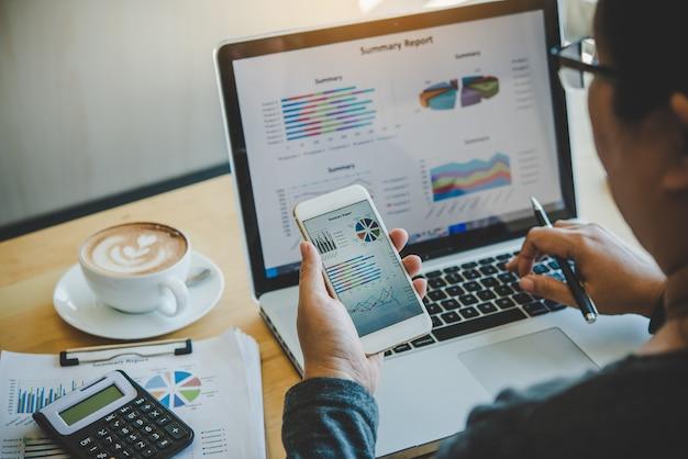 Gli uomini d'affari utilizzano smartphone e laptop per connettersi e trovare informazioni in ufficio