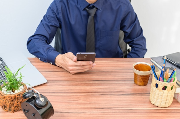 Gli uomini d'affari usano gli smartphone alla scrivania nella stanza