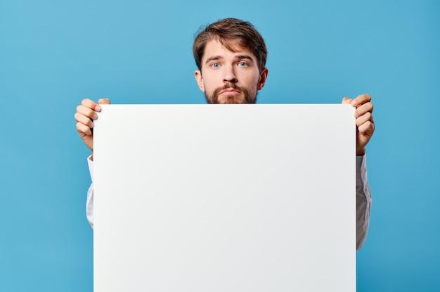 Manifesto bianco del modello degli uomini d'affari in mano che fa pubblicità allo sfondo isolato