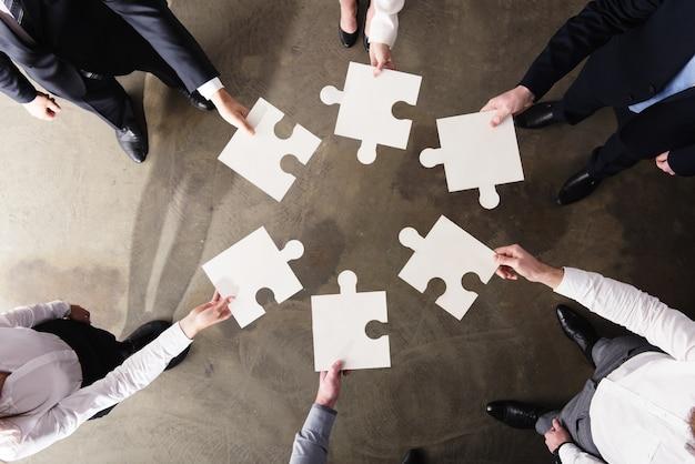 Uomini d'affari che lavorano insieme per costruire un grande puzzle. concetto di lavoro di squadra, partnership, integrazione e avvio.
