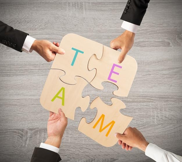 Uomini d'affari che lavorano insieme per costruire un puzzle colorato. concetto di squadra che lavora insieme