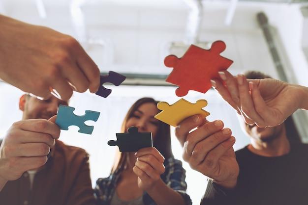 Uomini d'affari che lavorano insieme per costruire un puzzle
